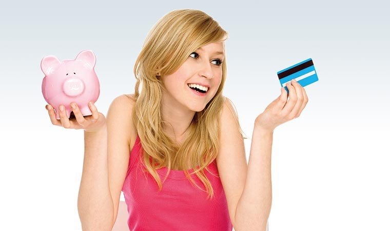 Young woman holding credit card and piggypank