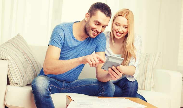 Young smiling couple with calculator and paperwork