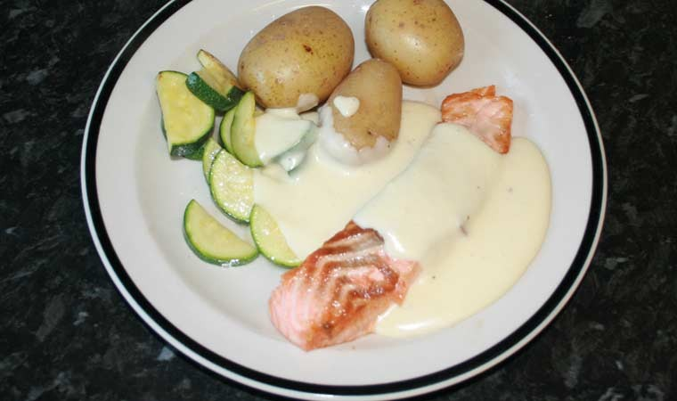 White sauce on salmon and vegetables