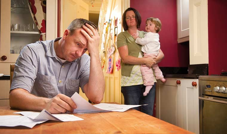 Unhappy husband looking at bills while wife holding baby looks on