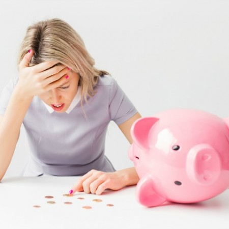 Unhappy woman with piggy bank and coins