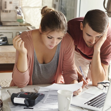 Young Married Couple With Many Debts Doing Paperwork Together