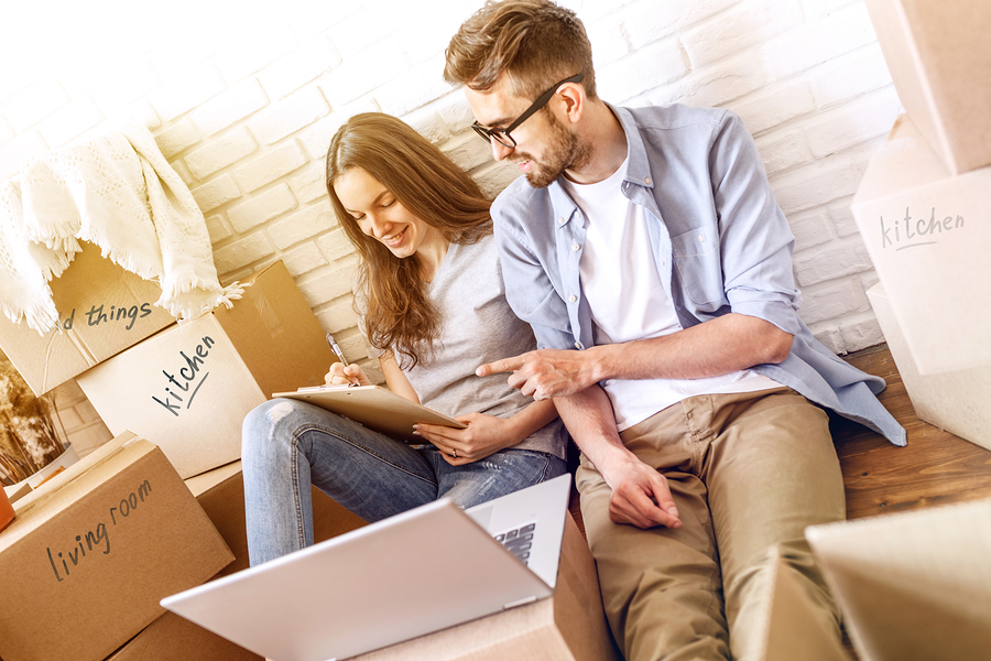 Young man and woman surrounded by packing boxes looking at checklist