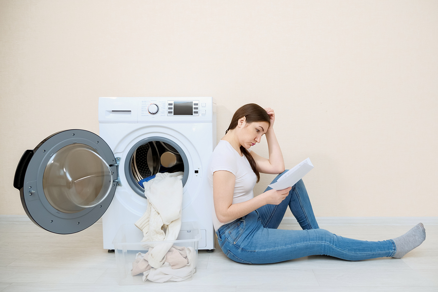 Young woman sitting against open washing machine
