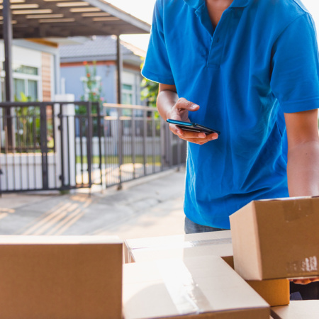Delivery man online holding deliveries out boxes and using mobile phone