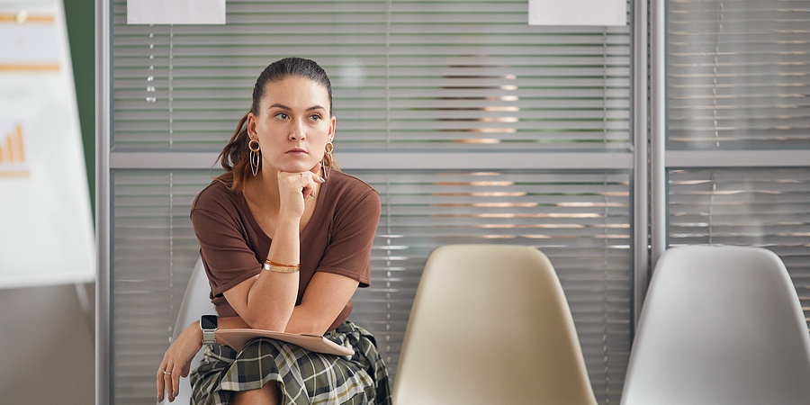 Nervous young woman waiting outside office for her job interview
