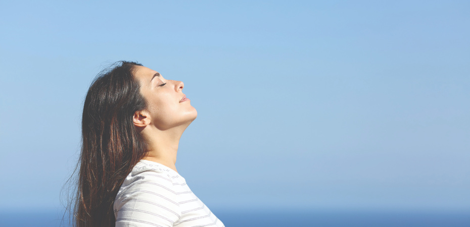 Young woman breathing deeply outdoors