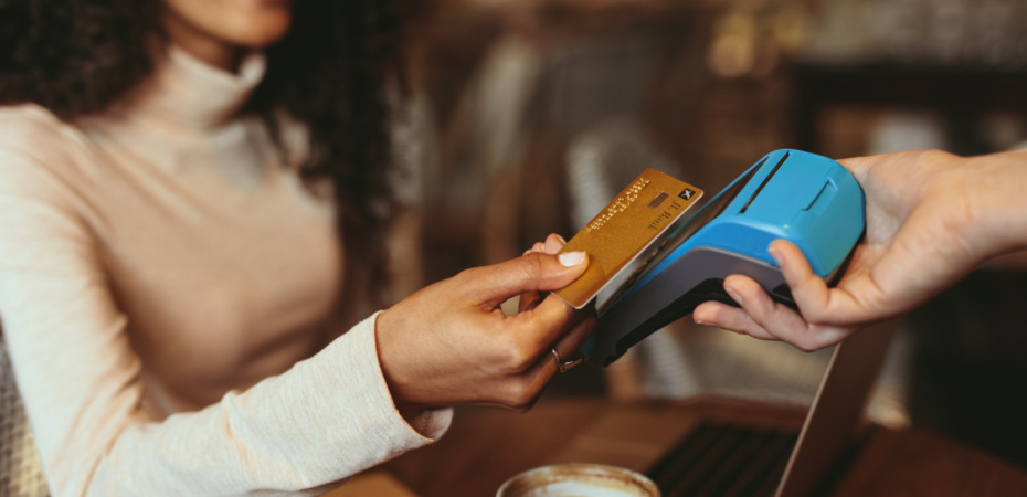 Woman using contactess credit card in a cafe