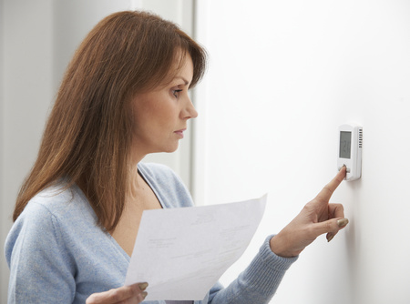 Woman adjusts her home thermostat
