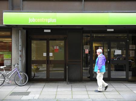 Older man walks past UK jobcentre