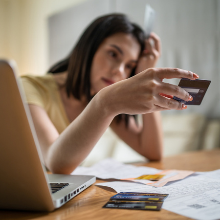 Unhappy young woman with bills and credit card